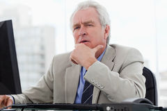 Thoughtful senior manager working with a monitor Royalty Free Stock Photography