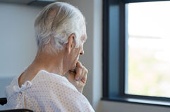 Thoughtful senior patient. Rear view of a senior man sitting on wheelchair looking outside the window. Old man in hospital room sitting near window and thinking Royalty Free Stock Photography
