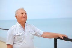 Thoughtful senior on veranda near seacoast Stock Photography