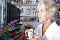 Thoughtful senior woman looking away while holding coffee cup in kitchen Royalty Free Stock Photography