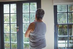 Thoughtful senior woman looking through window in bed room Royalty Free Stock Photos