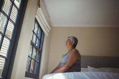 Thoughtful senior woman looking through window in bed room Stock Photo