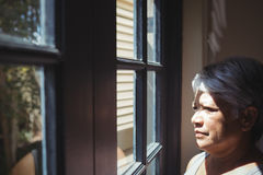 Thoughtful senior woman looking through window in bed room Royalty Free Stock Photography