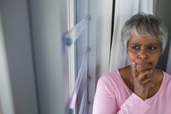 Thoughtful senior woman looking through window in bed room Stock Photos
