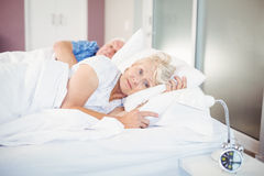 Thoughtful senior woman lying besides man on bed. Thoughtful senior women lying besides men on bed in room Royalty Free Stock Photography