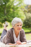 Thoughtful senior woman lying at park Royalty Free Stock Photos