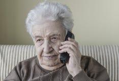 Thoughtful senior woman on phone Stock Photography