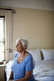 Thoughtful senior woman sitting on bed in the bedroom Royalty Free Stock Photography