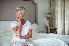 Thoughtful senior woman sitting in bed room Royalty Free Stock Photos