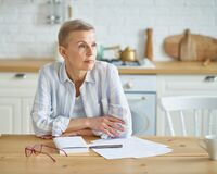 Free Thoughtful Senior Woman Thinking About Something While Sitting In Kitchen And Working With Documents Stock Images - 217517524