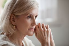 Thoughtful serious anxious mature senior woman feeling worried a stock images