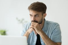 Thoughtful serious man lost in thoughts in front of laptop. Thoughtful serious young man lost in thoughts in front of laptop, focused businessman or absent Royalty Free Stock Photos