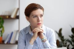 Thoughtful serious pensive businesswoman lost deep in thoughts at work stock photography