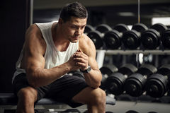 Thoughtful serious sportsman sitting in a gym. After a workout. Tired serious good looking man holding his hands together and thinking while finishing his Royalty Free Stock Photo