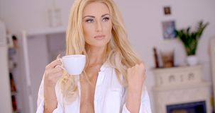 Thoughtful Sexy Blond Woman with a Cup of Coffee. Close up Thoughtful Sexy Blond Woman Holding a Cup of Coffee at the Living Room While Looking Afar Royalty Free Stock Image