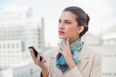 Thoughtful smart brown haired businesswoman holding a mobile phone Stock Image