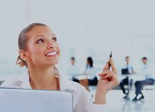 Thoughtful smiling business woman on the background of colleagues in the office. Royalty Free Stock Photography