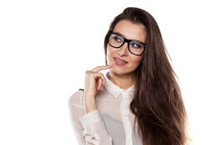 Thoughtful and smiling. Thoughtful smiling girl with eyeglasses posing on a white background royalty free stock photos