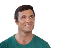 Thoughtful smiling mature man wearing green casuals. Looking up against white background Stock Images