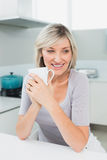 Thoughtful smiling woman with coffee cup in kitchen Royalty Free Stock Images