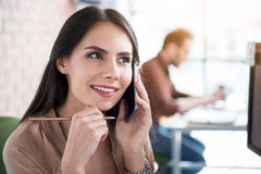 Thoughtful smiling woman keeping phone Royalty Free Stock Photos