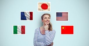 Thoughtful smiling woman standing by flags against blue background Stock Photography