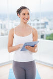 Thoughtful sporty model scrolling on tablet pc Stock Photography