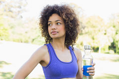 Thoughtful sporty woman holding water bottle Stock Images