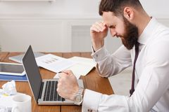 Tired businessman at desk with laptop searching way out from difficult situation. Close up, crop. Thoughtful stressed frustrated man working for too long on Stock Photos