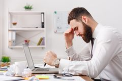 Tired businessman at desk with laptop searching way out from difficult situation. Thoughtful stressed frustrated man working for too long on computer, chooses Royalty Free Stock Photo