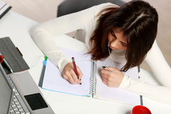 Thoughtful student doing her homework Stock Photo
