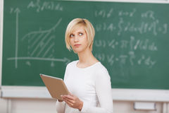 Thoughtful student holding tablet-pc. Thoughtful female student holding tablet-pc in classroom royalty free stock photography