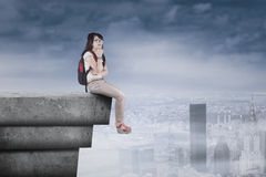 Thoughtful student sitting on high rooftop Royalty Free Stock Image