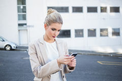 Thoughtful stylish businesswoman sending a text Stock Photo