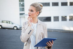 Thoughtful stylish businesswoman using digital tablet Royalty Free Stock Images