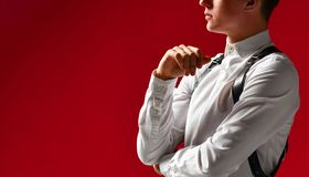 Thoughtful stylish handsome young man in a white shirt and a sword belt, on a red background stock images
