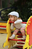 Thoughtful stylish one year old girl in a cap riding a toy hedgehog royalty free stock images