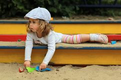 Thoughtful stylish one year old girl in a checked cap climbing out of a sandbox on a playground royalty free stock images