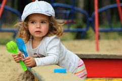Thoughtful stylish one year old girl in a checked cap climbing out of a sandbox stock images