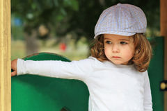 Thoughtful stylish one year old girl in a checked cap sitting on playground stock images