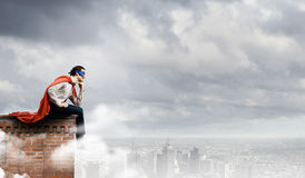 Thoughtful superman. In cape and mask sitting on top of building Royalty Free Stock Image