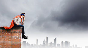 Thoughtful superman. In cape and mask sitting on top of building royalty free stock photography