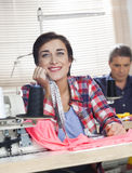Thoughtful Tailor Leaning On Workbench In Sewing Factory. Thoughtful female tailor leaning on workbench at sewing factory with colleague working in background Royalty Free Stock Photos