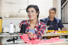 Thoughtful Tailor Sitting At Workbench In Sewing Factory. Thoughtful female tailor sitting at workbench in sewing factory with colleague working in background Royalty Free Stock Photos
