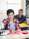 Thoughtful Tailor Smiling At Workbench In Sewing Factory Royalty Free Stock Photo