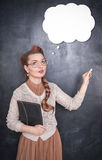 Thoughtful teacher in glasses with piece of chalk royalty free stock photo