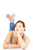Thoughtful teen girl lying on her tummy Stock Photos