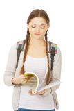 Thoughtful teen woman reading her notebook. Stock Photos