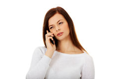 Thoughtful teen woman talking through a mobile phone Stock Photography