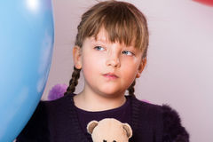 Thoughtful teenage girl on blue big rubber ball. Background. Child with pigtails in the studio Stock Photography
